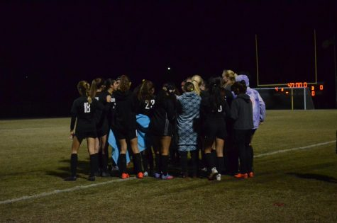During a water break, the team huddles to discuss their next play.