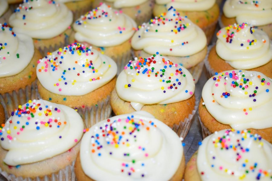 Confetti cupcakes decorated with cream cheese frosting and rainbow sprinkles.