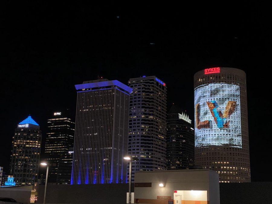 A Super Bowl LV ad projected onto a building in Downtown Tampa, as seen from the Super Bowl Experience.