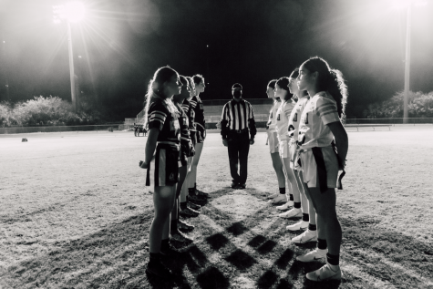 The Ravens and Knights line up to face off with crisscrossing shadows, a referee in between (All participants took a rapid COVID-19 test before working on the shoot).