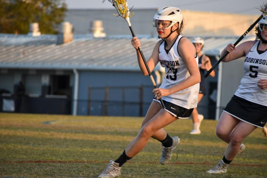 Maddie Berg ('24) dodges Alonso players while carrying the ball in her stick.