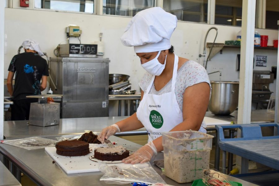 Nyema Kicks ('23) frosting the bottom layer of a chocolate cake with cookies and cream frosting.
