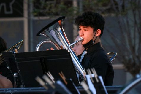 The sun hits Cole Rigg's ('23) face as he plays his euphonium.