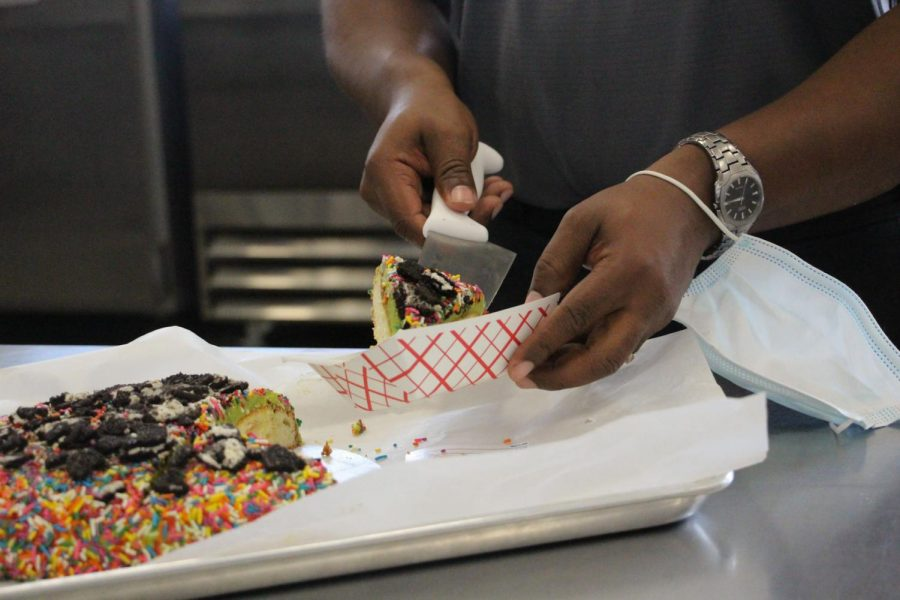 A judge gathers a slice of rainbow cake, decorated with sprinkles and Oreos. Judges were instructed to take samples of each cake and rank them on a set of criteria.