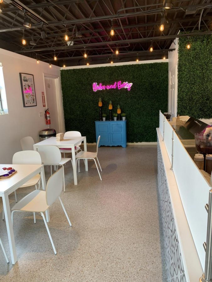 The interior of Boba and Berry is decorated with an LED sign, lush greenery and a clean color scheme of white tables and chairs.