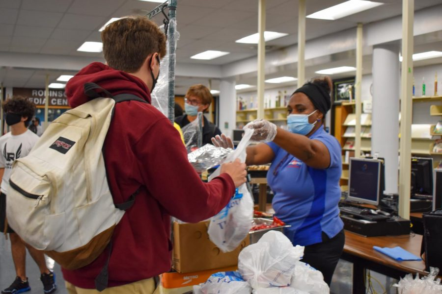 """Nicholas DeLise ('23) grabs his lunch from one of the carts around the school, The grab-and go-lunch consisted of a cheese pizza, apple slices, milk and a Rice Krispie. """"I feel like [grab-and-go] lunches are a safer way to get food to the kids who don't bring lunch. Not much of the food quality has been sacrificed in implementing them,"""" DeLise said."""