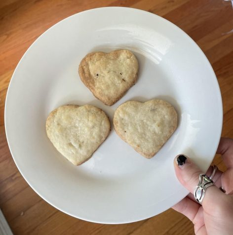 Heart-shaped lavender shortbread cookies with golden brown edges, arranged on a plate.