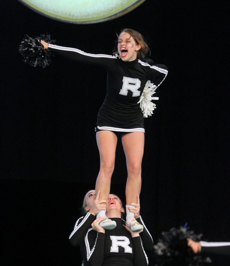 Hoisted in the air by her teammates, Alison Quigley ('22) chants during a routine.