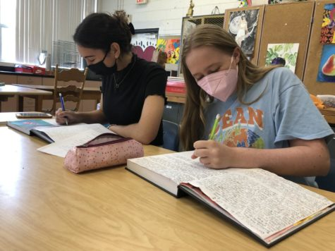 Students (left to right) Grace Barrett ('23) and Madelyn Ruyle ('23) mask up while working on art.